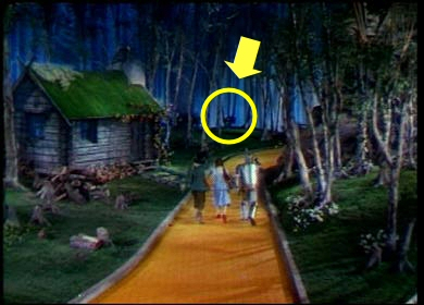 Picture of all four going down yellow brick road and the famous hangning in the background of the set
